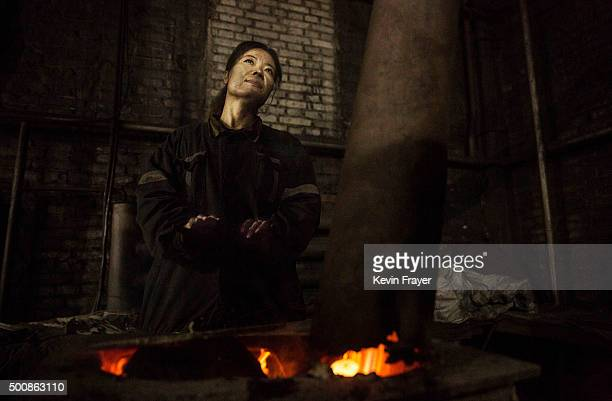 A Chinese mine worker warms herself over a coal stove coal as she takes a break at a mine on November 25 2015 in Shanxi China A history of heavy...