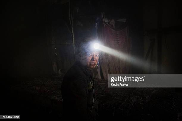 A Chinese miner smokes as he wears a headlamp while working at a coal mine on November 26 2015 in Shanxi China A history of heavy dependence on...