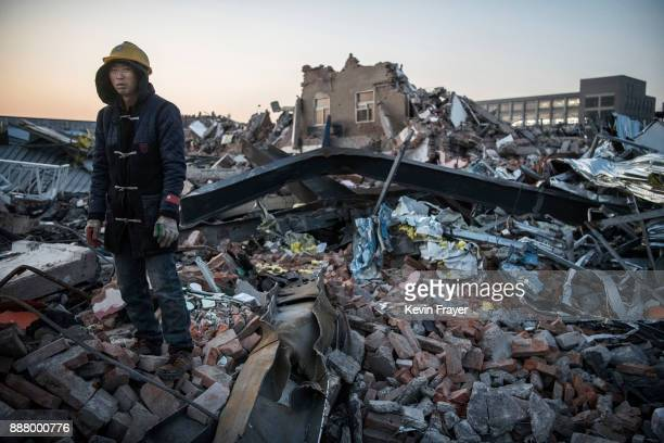 Chinese miworker salvages items from buildings demolished by authorities in an area that used to have migrant housing and factories on December 6...