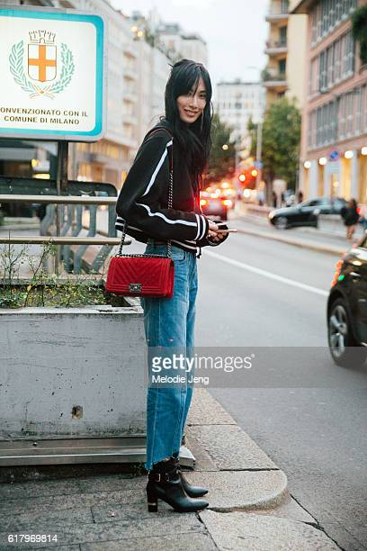 Chinese model Dylan Xue a black hooded shirt a red Chanel purse frayed jeans and black booties after the Fausto Puglisi show during Milan Fashion...
