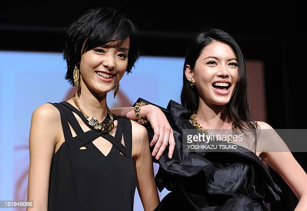 Chinese model Emma Pei and Thai model Davika Hoorne smile as they pose during the launch of Shiseido's skincare cream Za at a press preview in Tokyo...
