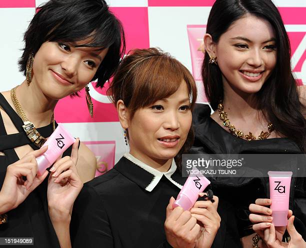 Chinese model Emma Pei and Thai model Davika Hoorne smile with Olympic volleyball bronze medallist Yoshie Takeshita of Japan as they pose with...