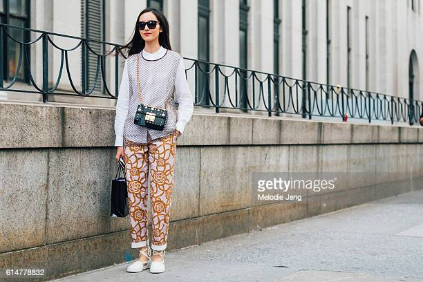 Chinese model Fei Fei Sun wears black sunglasses, a fishnet-style top over a white skirt, a black rectangular leather purse with gold embellishments,...