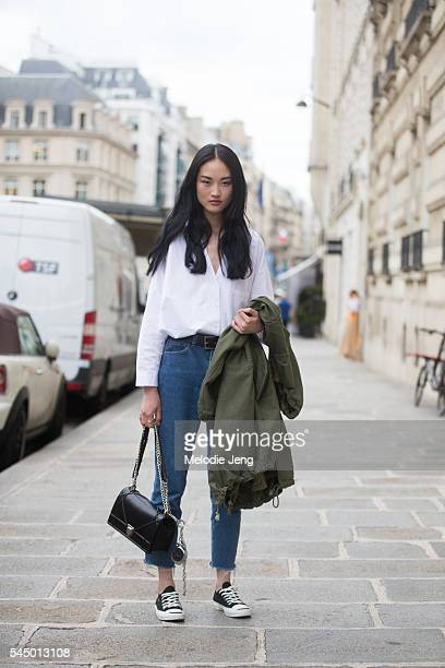 Chinese model Jing Wen wears a white buttonup shirt tucked into highwaisted jeans carries a Dior bag and wears Comme des Garcons x Converse sneakers...