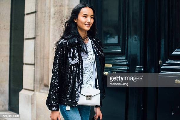 Chinese model Luping Wang wears a black sequined jacket and a white Prada purse after the Alberta Ferretti show on Day 1 of Couture FW 16 on July 03...