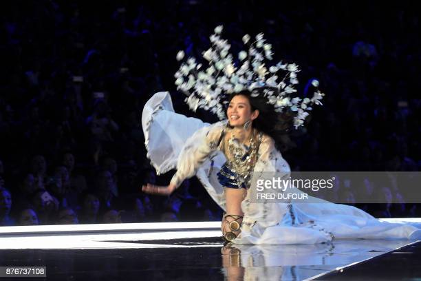 TOPSHOT Chinese model Ming Xi falls as she presents a creation during the 2017 Victoria's Secret Fashion Show in Shanghai on November 20 2017 / AFP...