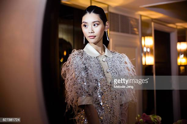 Chinese model Ming Xi wears a Michael Kors Collection whiteand silver sequinand ostrich featherembroidered tweed organza shirtdress De Beers diamond...