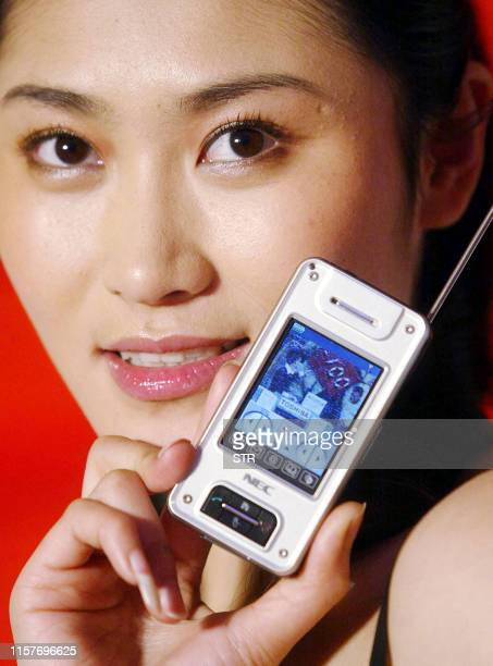 A Chinese model shows off the latest Japanese electronics giant NEC's N940 mobile phone with a builtin television in Beijing 26 January 2005 Japanese...