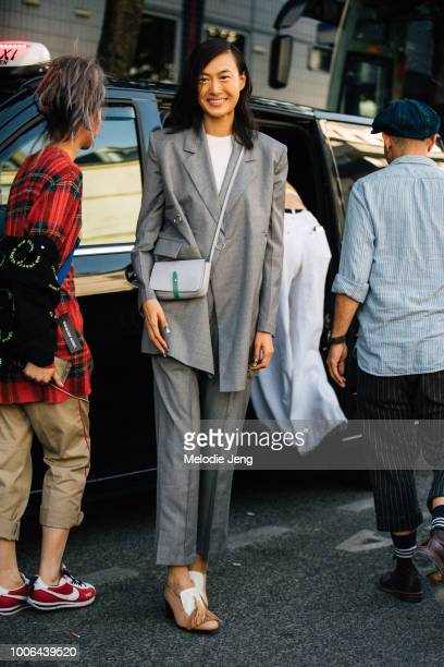 Chinese model Shu Pei Qin wears an oversized gray suit jacket and pants gray purse and brown toggle loafers after the Alyx show Chduring Paris...
