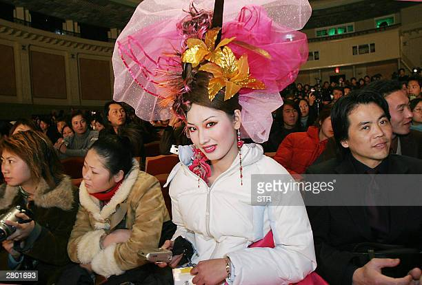 Chinese model sits with the audience with the latest hairdo and beauty makeup by local designers at a hair dressing and cosmetology exhibition in...