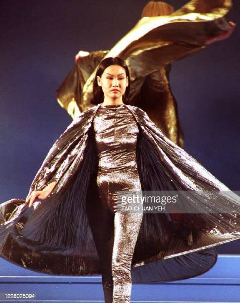 Chinese model strolls down the catwalk as she shows 11 March 1993 a gold- and-silver-catsuit and cape combination by French designer Pierre Cardin,...