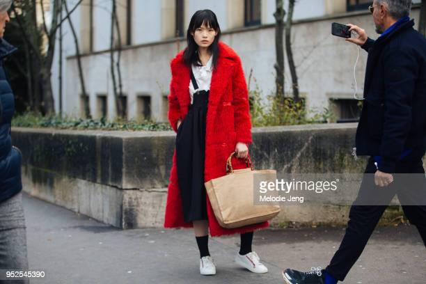 Chinese model Xie Chaoyu poses inbetween people walking by and taking photos in a long red fur coat white shirt black suspender pants white sneakers...