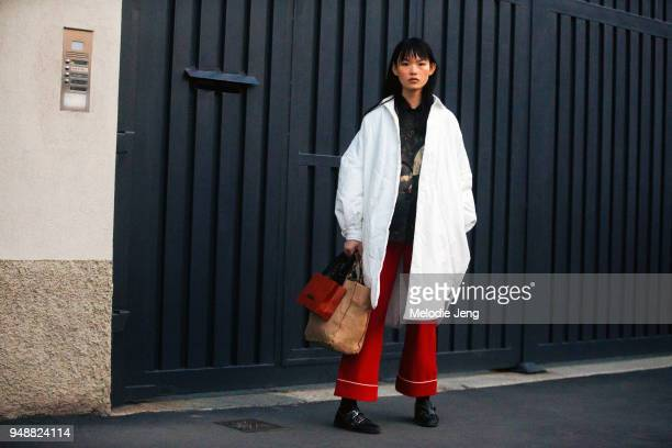 Chinese model Xie Chaoyu wears an oversized round white coat a black print top red flare pants and black shoes after the Missoni show during Milan...