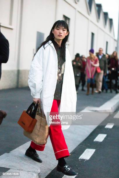 Chinese model Xie Chaoyu wears an oversized white coat and red pants during Milan Fashion Week Fall/Winter 2018/19 on February 24 2018 in Milan Italy