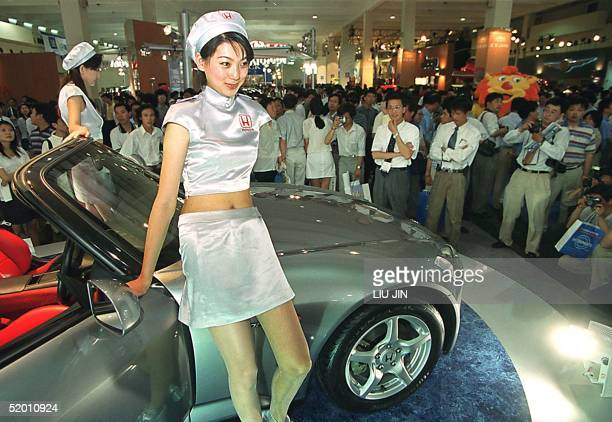 Chinese models pose while introducing a car at China's top car show of the year, Auto Shanghai, which kicked off 15 June 1999. More than 400 vehicle...
