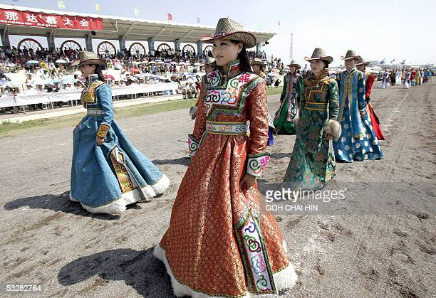 Chinese Mongolian models show off the various traditional outfits during a parade to mark the start of the Naadam festival on the grassland of...