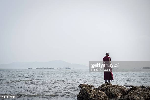A Chinese monk stares at the sea in Qingdao eastern China's Shandong province on July 24 2015 AFP PHOTO / FRED DUFOUR