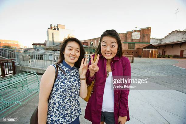 Chinese mother and daughter making peace sign