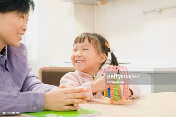mãe chinesa e filha jogo jogando juntos - conta artigo de armarinho - fotografias e filmes do acervo
