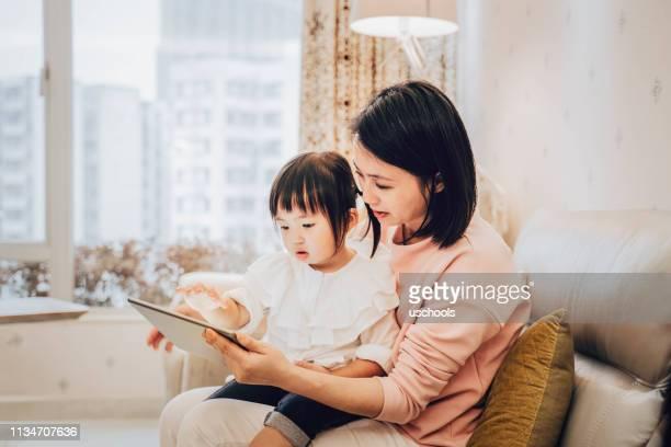 chinese mother and daughter using digital tablet - chinese culture stock pictures, royalty-free photos & images