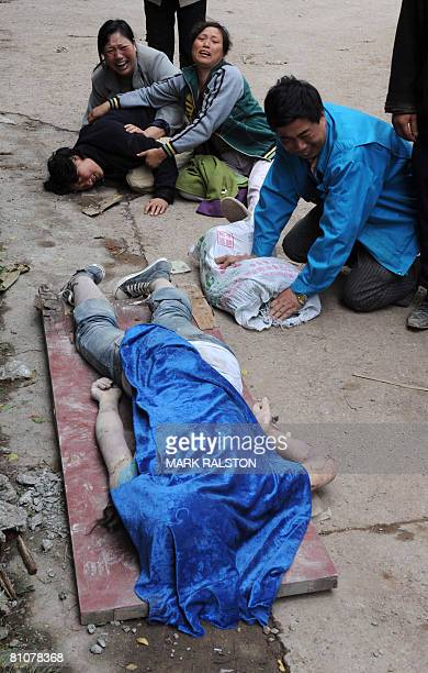 A Chinese mother and her relatives cry over the body of her child which was removed from a high school that collapsed after a 78 magnitude earthquake...