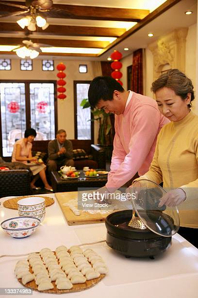 Chinese mother and her son making Chinese dumpling on New Years Eve