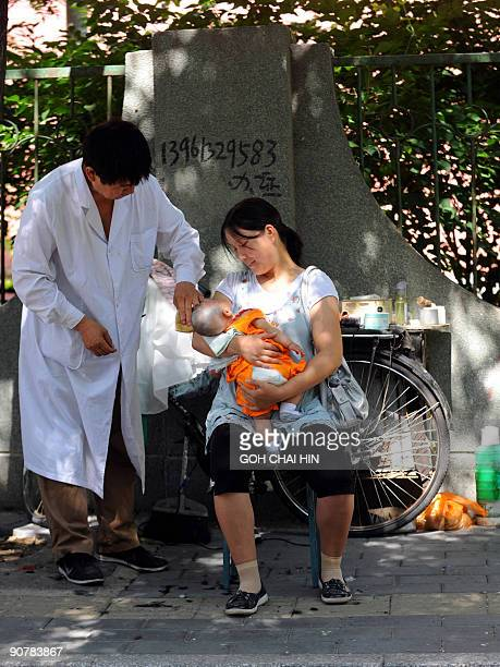 A Chinese mother carries her baby for his first hair trim along a street in Beijing on September 15 2009 The number of newborns with birth defects in...