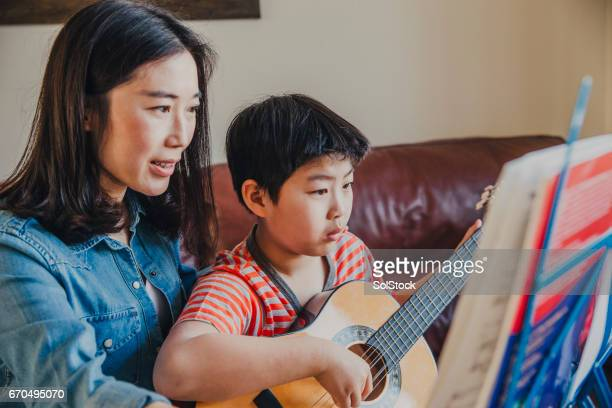 Chinese Mother Helping Son Learn Guitar