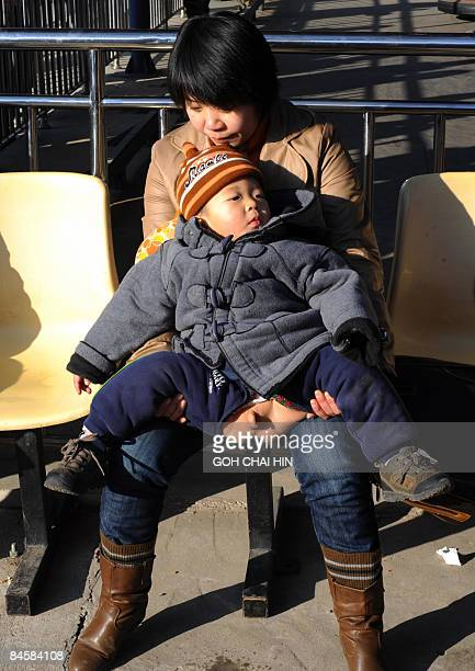 A Chinese mother waits for her young child to finish peeing as they visit a Lunar New Year festival at a park in Beijing on January 26 2009 The...