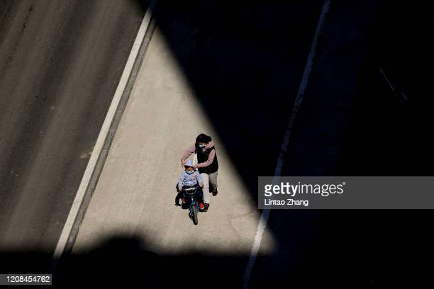 Chinese mother wears a protective mask as she with her child walks through the shadows from the between two buildings on March 28 2020 in Beijing...