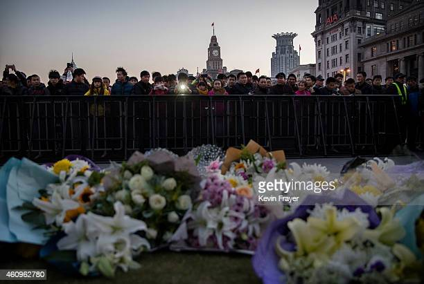 Chinese mourners gather at a makeshift memorial at the site of a stampede on January 1 2015 on the Bund in Shanghai China More than 35 people died...