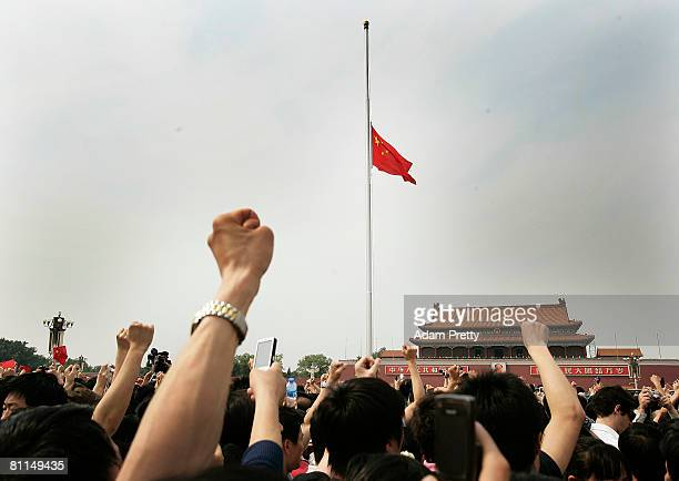 Chinese mourners show their support by cheering for the Sichuan Earthquake victims while the Chinese national flag flies at halfmast at the Great...