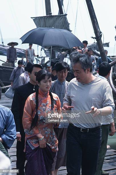 Chinese movie director Chen Kaige gives instructions to actress Gong Li during the filming of 'Temptress Moon' Actor Leslie Cheung Kwok Wing walks...