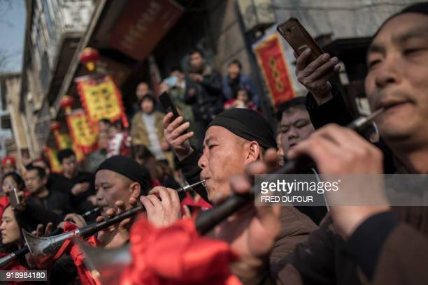 Chinese musicians dressed with a traditional costume attend a wedding performance as part of the She Huo festival to celebrate the Lunar New Year...