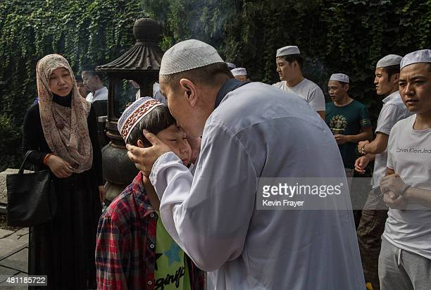 Chinese Muslim Imam of the Hui ethnic minority kisses a young worshipper after blessing him before Eid Al Fitr prayers marking the end of the holy...