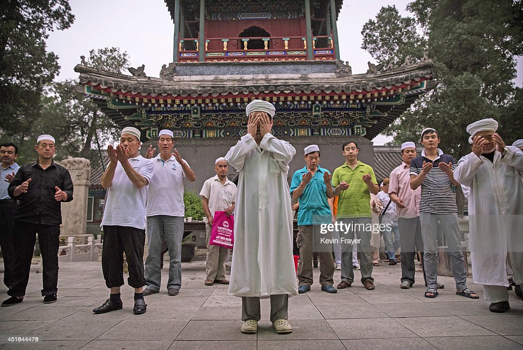 A Chinese Muslim Imam of the Hui ethnic minority leads prayers before breaking fast during the holy fasting month of Ramadan at the historic Niujie Mosque on July 3, 2014 in Beijing, China. The Hui Muslim community, which numbers more than an estimated 10 million throughout the country, is predominantly Chinese-speaking. Muslims around the world are marking Ramadan, where the devout fast from dawn until dusk, and is a time of fasting, prayer and charitable giving.