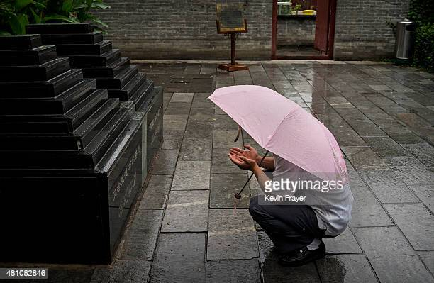 Chinese Muslim of the Hui ethnic minority prays under an umbrella in the rain at the Imam's Tomb before the last Friday prayers of the holy fasting...