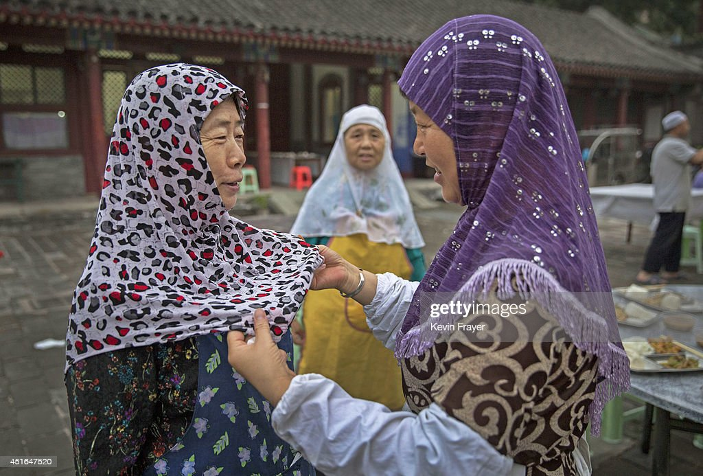 A Chinese Muslim woman of the Hui ethnic minority has her headscarf adjusted as they prepare to break fast during the holy fasting month of Ramadan at the historic Niujie Mosque on July 3, 2014 in Beijing, China. The Hui Muslim community, which numbers more than an estimated 10 million throughout the country, is predominantly Chinese-speaking. Muslims around the world are marking Ramadan, where the devout fast from dawn until dusk, and is a time of fasting, prayer and charitable giving.