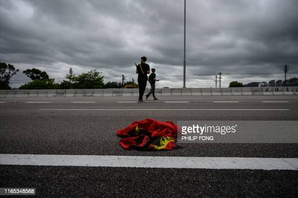 A Chinese national flag burnt by protesters is seen on a road leading to Hong Kong International Airport on September 1 2019 Thousands of Hong Kong...