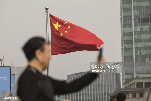 A Chinese national flag flies as a man uses a smartphone in Shanghai China on Tuesday Nov 27 2018 Apple which has lost a fifth of its value in a tech...