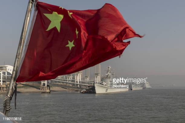 Chinese national flag flies from a ferry as the retired People's Liberation Army Navy Xian frigate ship, from left, and the Huaian frigate ship sit...