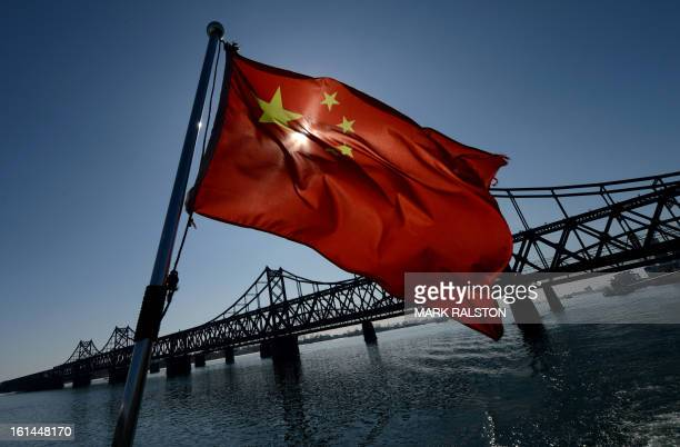 A Chinese national flag flies on a boat before the SinoKorean Friendship bridge that spans the Yalu River linking the North Korean town of Sinuiju...