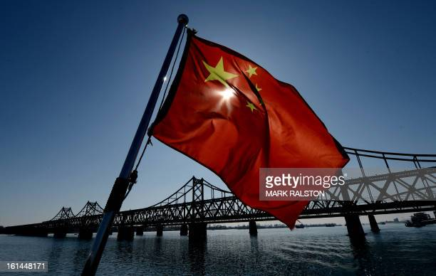 Chinese national flag flies on a boat before the Sino-Korean Friendship bridge that spans the Yalu River linking the North Korean town of Sinuiju...