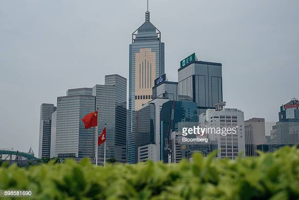 A Chinese national flag left and a Hong Kong SAR flag fly in front of the Central Plaza center and other buildings in Hong Kong China on Wednesday...