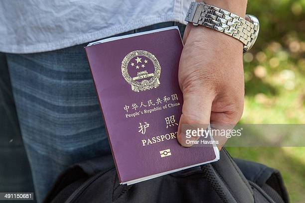 Chinese national holds a Chinese Passport after being stamped to enter Cambodia after fleeing Vietnam on May 16 2014 at the Bavet border crossing...