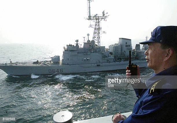 Chinese naval officer communicates with his French counterparts during a joint exercise 16 March 2004 in the East China Sea off the coast of eastern...