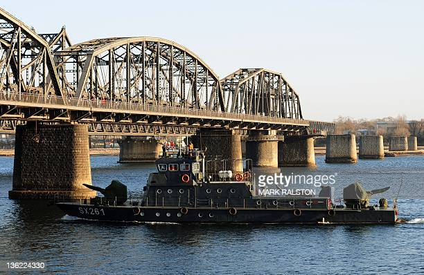 A Chinese navy boat patrols beside the old Yalu Bridge on the Yalu River on the day of the memorial service for the late leader Kim JongIl at the...