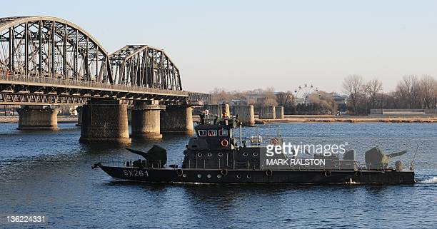 Chinese navy boat patrols beside the old Yalu Bridge on the Yalu River on the day of the memorial service for the late leader Kim Jong-Il, at the...
