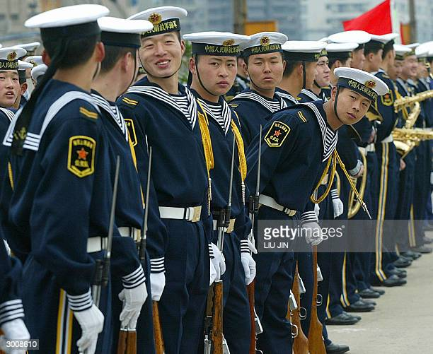 Chinese navy soldier leans out as other soldiers chat in a rank before the USS Blue Ridge arrives in Shanghai, 24 February 2004. The command ship of...