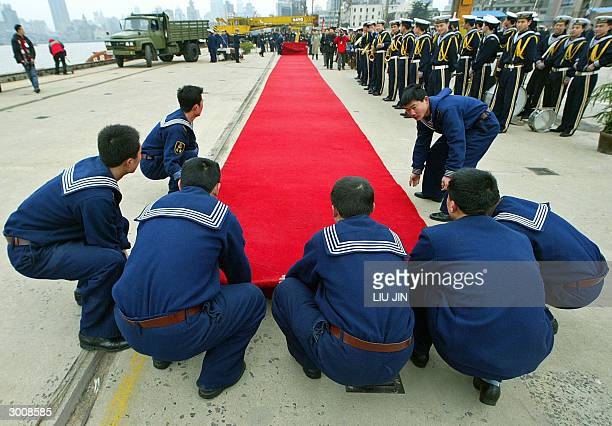 Chinese navy soldiers roll out the red carpet upon the USS Blue Ridge arrives in Shanghai, 24 February 2004. The command ship of the US Navy's...